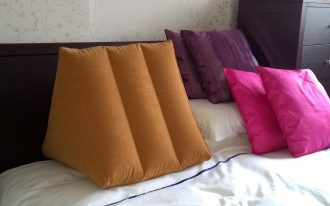 modern yellow sit up pillow design shaped in triple triangle on white bed with pink and purple pillows
