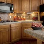 natural sand motive granite countertop for classic kitchen with small tile blocks walls and natural wooden cabinets