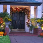 playful outdoor thanksgiving decoration idea before black wooden door with wreath and lighting track and pumpkins