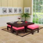 playful wooden deck coffee table design with pink stools on brown area rug with cream wall with palette and rustic tile flooring and open plan