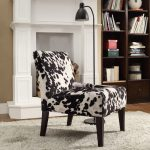 posh armless cow print chair design beneath curve black floor lamp on furry rug aside wooen bookshelves and fireplace