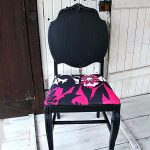 posh black painting fabric furniture idea with magenta accent and round carved backrest on white washed wooden floor aside farm door