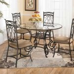 Pretty Round  Wrought Iron Kitchen Table With Glass Top In Dining Space And Cozy Seating Plus Brown Grey And Beige Rug Plus Plates Of Fruits