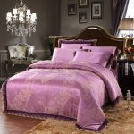 purple high end linens bedding set with luxury style and headboard plus brown rug and elegant crystal lighting and wooden nightstand