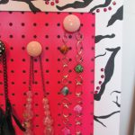 red pegboard jewelry display colorful necklaces tree branches motive wall