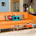 retro orange room to gos sofa design with loveseat design and colorful cushions and acrylic coffee table and patterned white area rug and gray wall