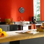 retro paint color for kitchen with orange tone and natural wooden table and sunflower and gray cabinetry and small clock and wine storage