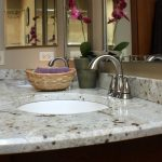 river white granite countertop  in small bathroom with round sink and curve faucet and wall mirror and rattan basket