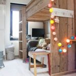 rustic bunk bed idea with colorful string light in bedroom with storage bin and glass window