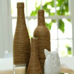 rustic wine bottle decorating ideas with jute yarn decoration sticked on the bottle in brown color on glass tray