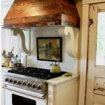 rustic wood vent hood for kitchen ideas with modern gas stove and adorned with picture on wall and white kitchen backsplash and kitchen cabinets