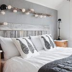 scandinavian bedroom design with white bedding and black sheet and rustic frame and wooden table and black table lamp and string light