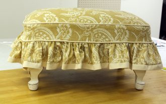 shabby chich ottoman slip covers with light brown and white pattern plus short woodem leg is also presented before