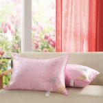 silky light pink pillow design on white sofa in open plan room with sheer red curtain