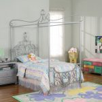 silver metal canopy bed frame pastel color cushion and bedsheet pastel color furniture decorative dolls princess style kids bedroom pastel flower carpet brown wooden floor