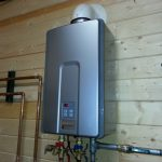 silver tankless water heater installed inside the house