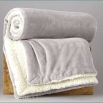 simple and posh faux sheepskin throw in white tone with rolled style on rustic wooden bench