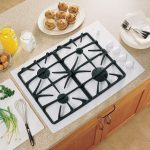 simple black and white 30 gas cooktop with downdraft white knobs natural soft stone kitchen surface milk and orange juice in jar plates and forks wooden furniture cute cakes and vegetable