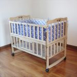 simple designed wooden crib size bunk bed design with blue patterned sheet and wheels and hardwood floor