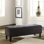 simple gray tufted bench for oversized accent chair with wooden legs on wooden floor with ceramic decoration and furry rug