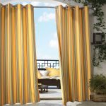 simple indoor outdoor curtain in yellow striped accent plus greenery and decorated with comfy wooden chair outside