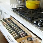 simple kitchen cabinet design with cook top and yellow pan and white wall and beige tone in drawer spice racks