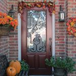 simple outdoor thanksgiving decoration idea on red brick wall with fall color flower and leave with pumpkin on the bench