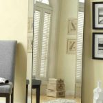 simple rectangle beveled floor mirror idea beneath cream wall with pictures and gray chair
