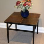 simple slate end tables with slate tiling plus pretty flower with blue vase as centerpiece decorated with rug under the table