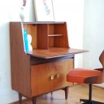 single mid century secretary desk design with top sorage and lower storage and swivel chair on hardwood floor