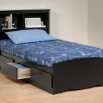 sleek simple black wooden twin headboard with shelves for books and notebook two tones blue bedding natural wooden floor classic white walls