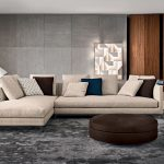 slim and low leg sectional sofa with single chaise and multiple colored throw pillows modern side tables modern standing lamp round ottoman furniture large grey wool area rug modern wall lighting
