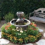 small garden idea with fountain in round bowl with low growing flowers and stone walkway and rustic bench aside lush vegetation