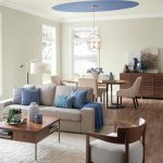 small home living wood floor grey sofa with blue pillows table with drawer decorative rug