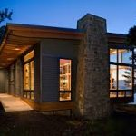 small lake house plan idea with stone wall accent and glass door and siding and wooden floor and modern lighting
