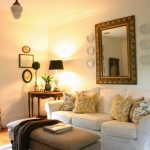 sophisticated living room with white slipcovered sofa and yellow and white paterned cushions plus brown ottoman coffee table plus floral curtain and wooden end table