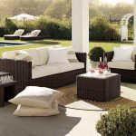 sophisticated outdoor living space design with natural rattan sofa with white bolster and boxy coffee table with shrub and green landscape and best patio furniture brands
