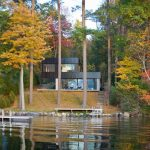 sophisticated small lake house design with black roof and open plan to view fall plants tone with lake deck