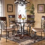 sophisticated wrought iron kitchen table in a round shape with wood top and brown patterned rug and chandelier hanging on ceiling and wood floor