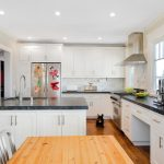 spacious kitchen design with white cabinetry and black giallo rio granite countertop and wooden dining table