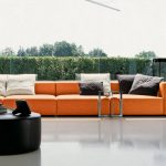 spacious open plan interior with room to go sofa design in orange color with round black coffee table with large floor to ceiling glass window