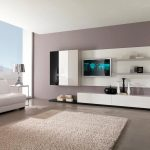 spacious open plan living space with white ikea tv stand and wall cabineta dn black chair and white sofa and creamy area rug