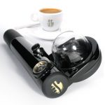 special designed black hand espresso maker with long handle and transparent accent and white cup of coffee