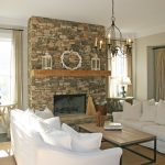 stone fireplace sofas table pillows curtains rug lamp chandelier