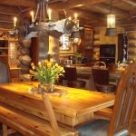 stunning log cabin style home design with wooden dining table with chairs and bench and candle lighting and exposed beam ceiling