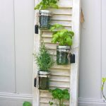 stunning vertical herb garden idea for apartment on white board with texture and transparant glass cans for outdoor