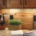 stylish vintage tile backsplash design beneath wooden storage with potted plant and giallo rio granite countertop