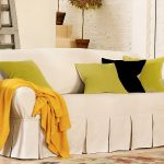 stylish white  pottery barn sofa slipcover design with green black cushions and yellow throw and patterned area rug and green coffee table and ladder storage and stairs