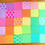 sweet baby quilt to make idea in pink yellow and blue gradation with plaid pattern on wooden floor in rectangle shapeq