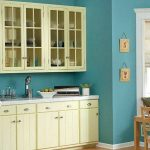 sweet painted blue color for kitchen design with white cabinetry and molding and wooden dining table and potted plant